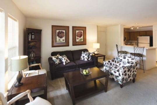 A beautifully furnished living room in the A1 floorplan at Crown Chase Apartments