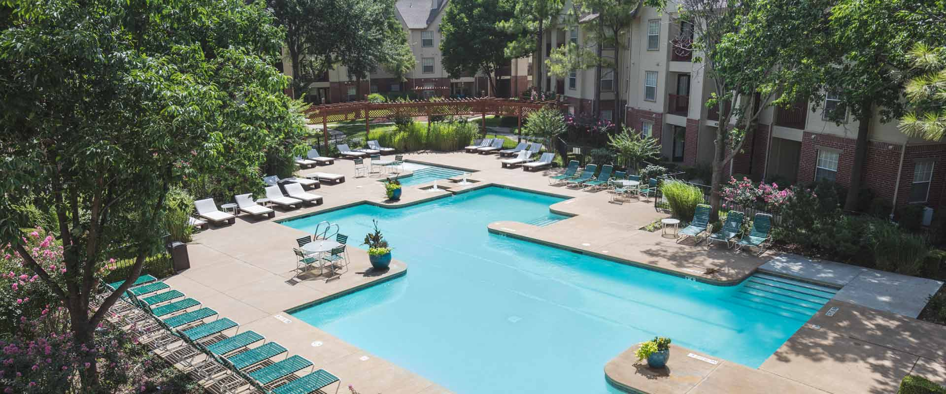 An aerial view of the Swimming Pool and sun deck at Crown Chase Apartments in Tulsa Oklahoma. There are flower shrubs and potted plants, a misting system and many lounge chairs.